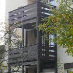 grünes Katzennetz an Holzbalkon im 2. Stock